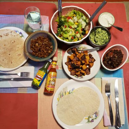 Tortillas, salad, beans, hot sauce, roasted sweet potatoes, guacamole