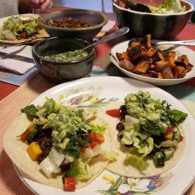 Corn tortillas with beans, vegetables, guacamole, and roasted sweet potatoes