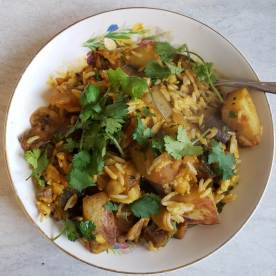 Eggplant chickpea curry with rice, crispy potatoes, and cilantro