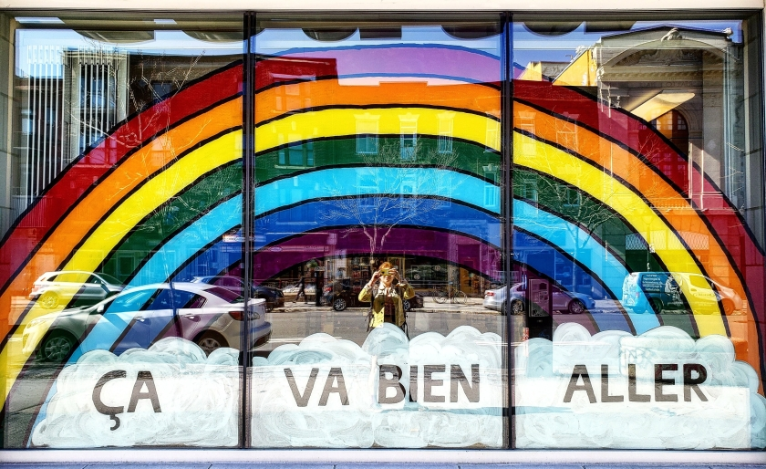 "Rainbow in store front window ""ca va bien aller"" with the reflection of a young woman, the photographer"