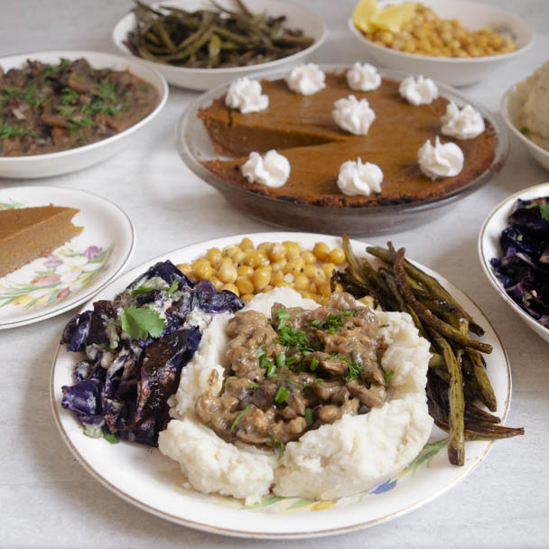 Vegan thanksgiving plate, mashed potatoes, mushroom sausage gravy, roasted green beans, roasted cabbage and chickpeas, pumpkin pie with coconut whipped cream